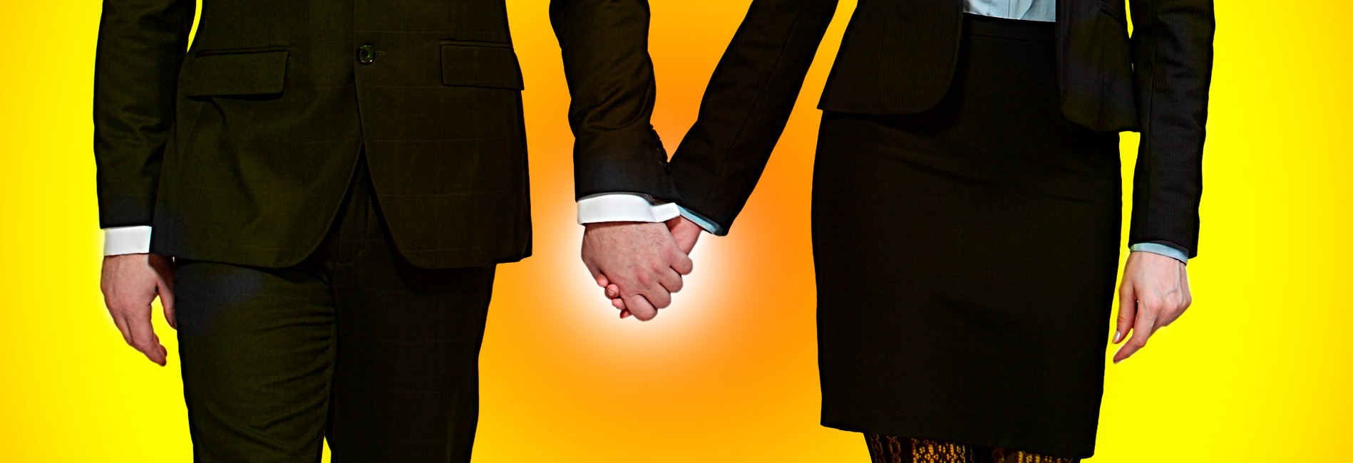 Couple in suits holding hands